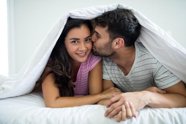 Homme, baisers, femme, sous couverture, dans, les, chambre à coucher, chez soi