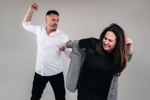 Un homme balance son poing sur une femme battue debout sur un fond gris. violence domestique