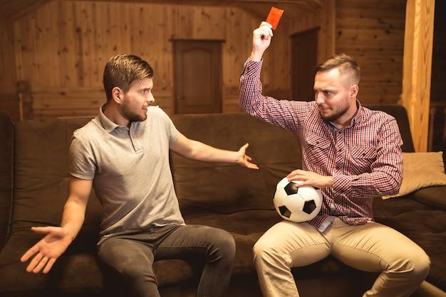 L'homme avec un ballon montre le carton rouge à son ami