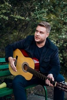 Homme sur un banc jouant de la guitare