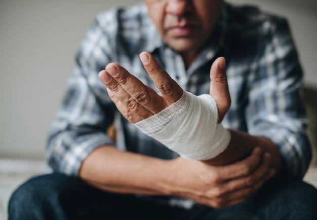 Homme avec un bandage de gaze enroulé autour de sa main