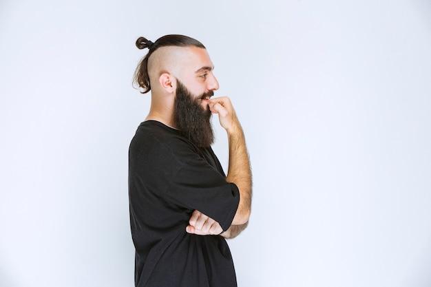 L'homme à la barbe a l'air pensif et rêveur.