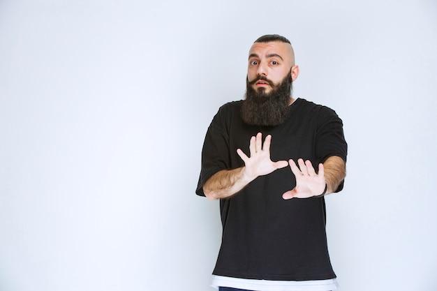 Homme avec barbe arrêtant quelque chose avec la main ouverte.