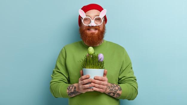 Homme à la barbe au gingembre portant des vêtements colorés et des lunettes oreilles de lapin