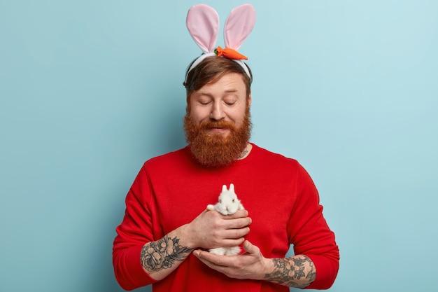 Homme avec barbe au gingembre portant des vêtements colorés et des oreilles de lapin tenant un lapin