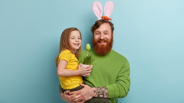 Homme à la barbe au gingembre portant des vêtements colorés et des oreilles de lapin tenant sa fille