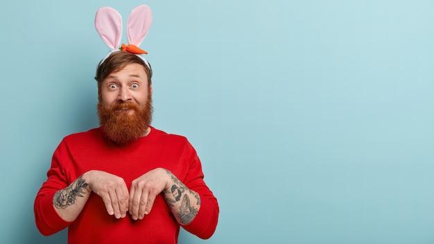 Homme à la barbe au gingembre portant des vêtements colorés et des oreilles de lapin