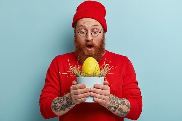 Homme avec barbe au gingembre portant des vêtements colorés et tenant l'oeuf de pâques