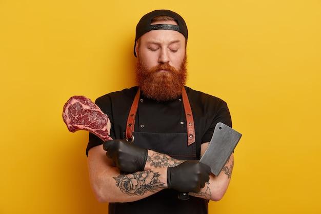 Homme avec barbe au gingembre en tablier et gants tenant la viande et le couteau