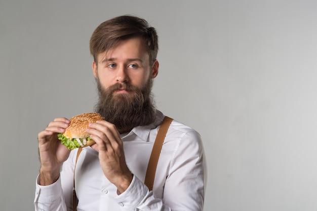 Homme avec barbe en chemise blanche et bretelles mangeant de la malbouffe d'un hamburger de restauration rapide ou d'un cheeseburger sur fond gris