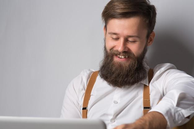 L'homme à la barbe en chemise blanche et bretelles travaille et communique dans un ordinateur portable sur fond gris