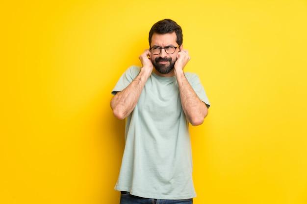 Homme à la barbe et chemise verte couvrant les oreilles avec les mains. expression frustrée