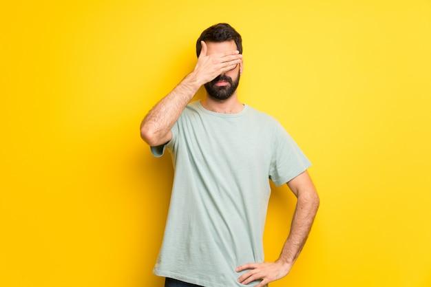 Homme à la barbe et chemise verte couvrant les yeux par des mains. je ne veux pas voir quelque chose