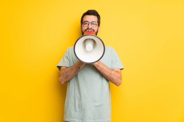 Homme à la barbe et à la chemise verte criant dans un mégaphone pour annoncer quelque chose