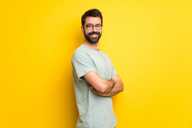 Homme à la barbe et à la chemise verte, gardant les bras croisés en position latérale tout en souriant
