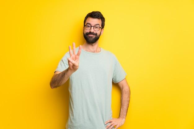 Homme à la barbe et à la chemise verte heureux et comptant trois avec les doigts