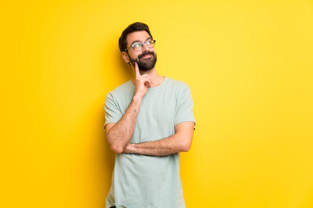 Homme à la barbe et à la chemise verte, pensant à une idée tout en levant les yeux