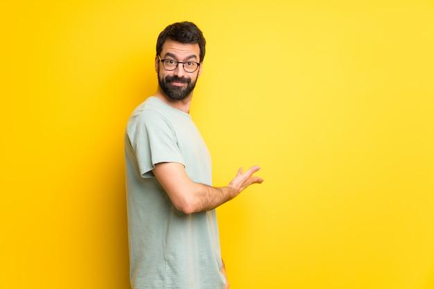 Homme à la barbe et chemise verte pointant en arrière et présentant un produit