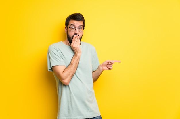 Homme à la barbe et chemise verte, pointant le doigt sur le côté avec un visage surpris