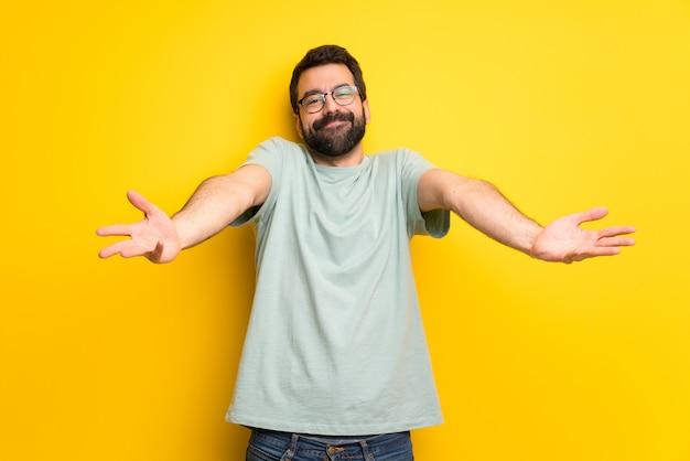 Homme à la barbe et à la chemise verte présentant et invitant à venir avec la main