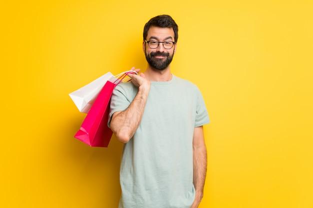 Homme à la barbe et chemise verte tenant beaucoup de sacs à provisions