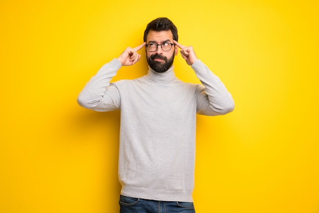 Homme avec barbe et col roulé ayant des doutes et penser