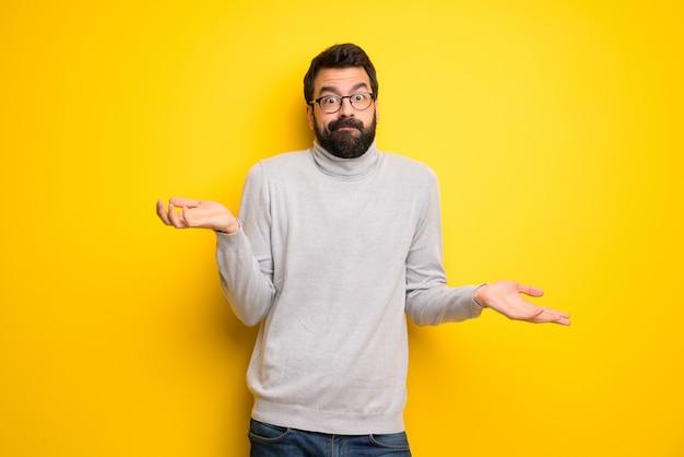 Homme avec barbe et col roulé ayant des doutes tout en levant les mains et les épaules