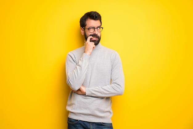 Homme à la barbe et col roulé ayant des doutes tout en levant les yeux