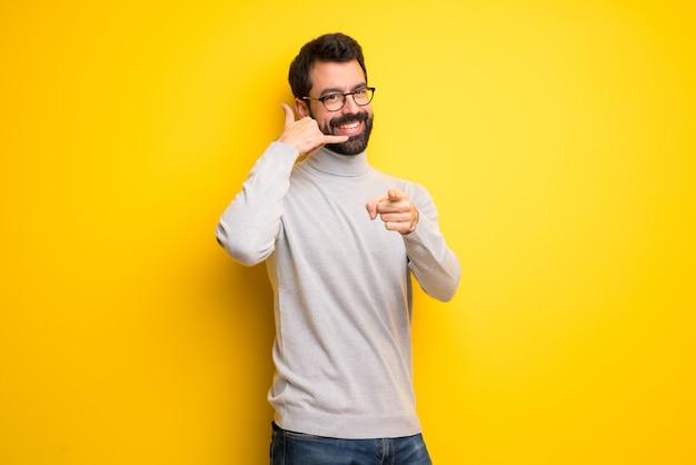 Homme avec barbe et col roulé faisant un geste de téléphone et pointant devant