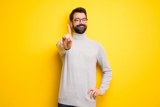 Homme à la barbe et col roulé montrant et en levant un doigt