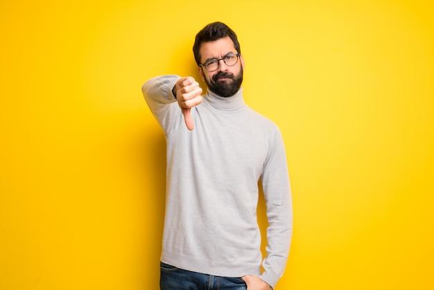 Homme à la barbe et col roulé montrant le pouce vers le bas de signe avec une expression négative