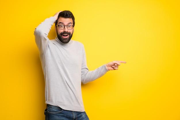 Homme avec barbe et col roulé, pointant le doigt sur le côté et présentant un produit