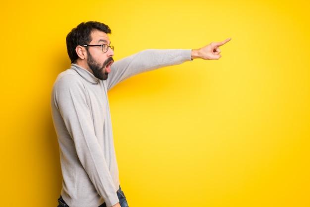 Homme avec barbe et col roulé pointant loin