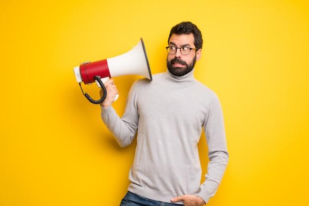 Homme avec barbe et col roulé prenant un mégaphone qui fait beaucoup de bruit
