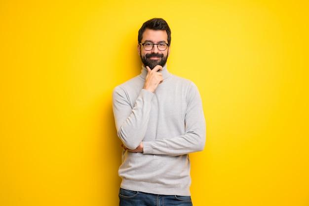 Homme avec barbe et col roulé souriant et regardant vers l'avant avec visage confiant