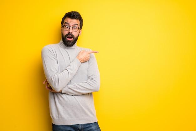 Homme à la barbe et col roulé surpris et pointant le côté