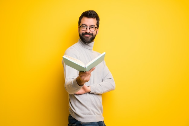 Homme à la barbe et col roulé tenant un livre et le donnant à quelqu'un
