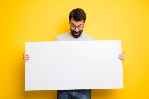 Homme à la barbe et col roulé tenant une pancarte pour insérer un concept