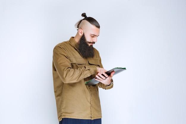 Homme à la barbe contrôlant les documents financiers.