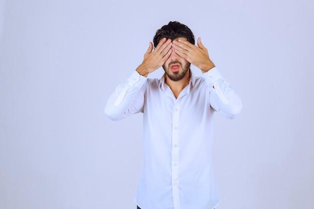 Homme avec barbe couvrant ses yeux car il est somnolent.