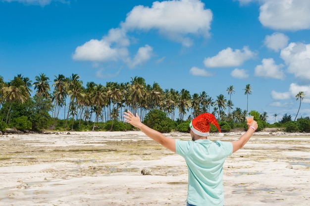 Un homme avec une barbe dans un chapeau de noël boit un cocktail sur la plage