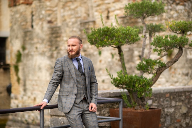 Un homme avec une barbe dans un costume trois pièces gris strict avec une cravate dans la vieille ville de sirmione, un homme élégant en costume gris en italie.