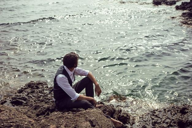 Homme avec une barbe dans des vêtements sombres et une chemise blanche est assis sur le bord de mer en pierre dans le tarkhankut de crimée