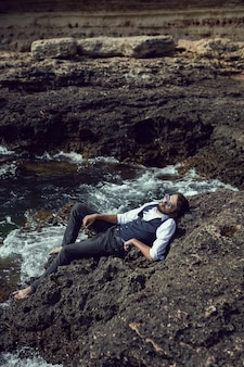 Homme avec une barbe dans des vêtements sombres et une chemise blanche des lunettes de soleil se trouvent sur le rivage de pierre dans le tarkhankut de crimée