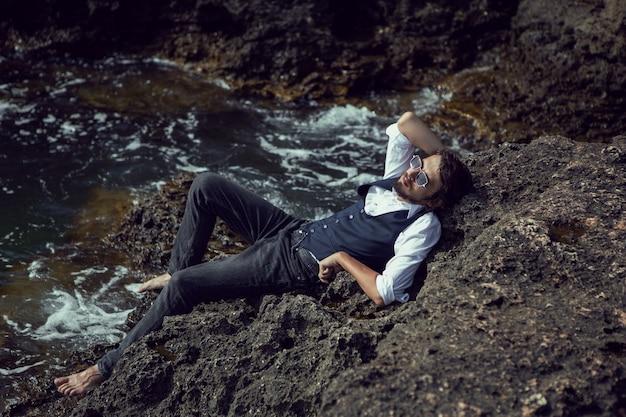Homme avec une barbe dans des vêtements sombres et une chemise blanche se trouvent sur le rivage de pierre en crimée tarkhankut