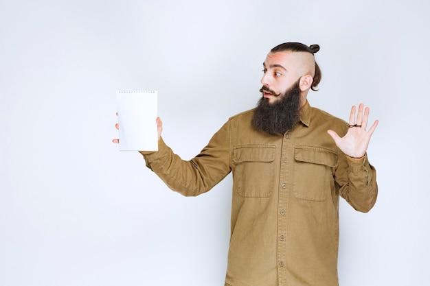 Homme à la barbe démontrant son projet et en attente d'avis.