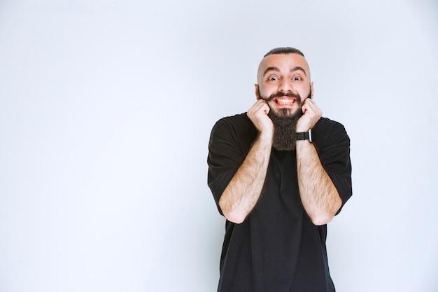 L'homme à la barbe devient extrêmement heureux à cause de quelque chose.