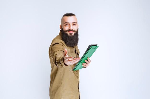 Homme à la barbe donnant sa liste de projets pour vérification.