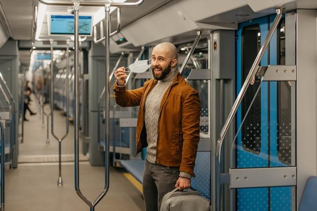 Un homme avec une barbe enlève un masque médical et sourit dans une voiture de métro. un homme chauve avec un masque chirurgical contre covid-19 garde une distance sociale dans un train.