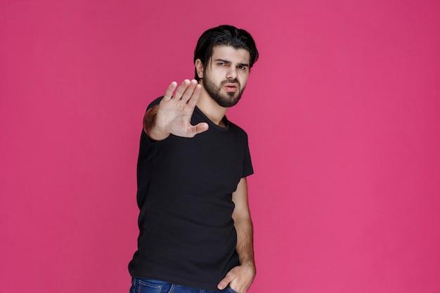 Homme à la barbe faisant signe de la main de rejet.